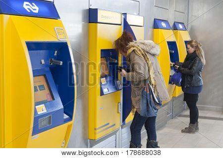 Utrecht Netherlands 15 march 2017: women buy tickets at machine on utrecht central station in the netherlands