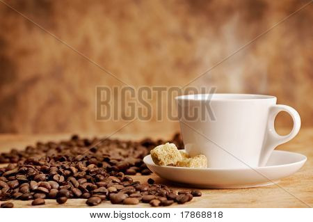 Coffee cup and roasted beans on vintage background