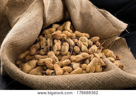 Peanuts in nutshell in sackcloth and black background
