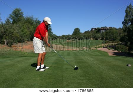 Male golfer with red shirt addressing ball about to tee off poster