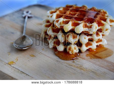Waffle with honey on a Board of wood and silver spoon.