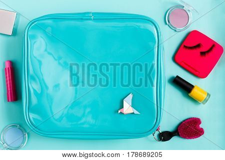 Beauty products. Cosmetic bag with  essentials - eyelashes, eyeshadow, lipstick and nail polish on blue background, flat lay, top view