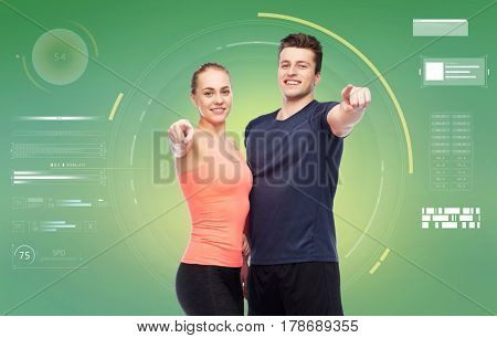 sport, fitness, technology and people concept - happy sportive man and woman pointing finger on you over green background