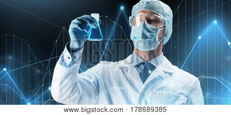 science, chemistry, research and people concept - young scientist in protective mask, hat and goggles holding test flask with chemical over dark background and virtual chart
