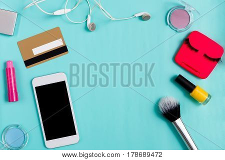 Beauty products online shopping, everyday make-up. Flat lay of cosmetic essentials, mobile phone, credit card and headphones on bright blue background, objects