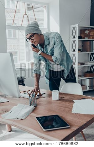 Concentrated on work. Serious young man talking on smart phone and using computer while standing near his desk in creative office