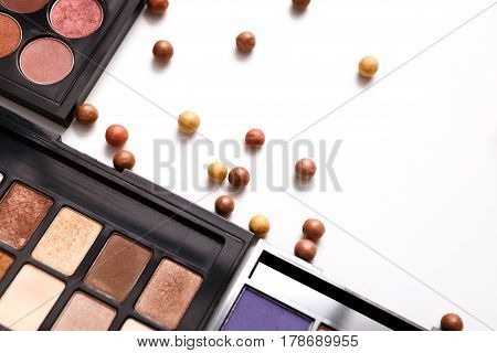 Makeup cosmetics and essentials white background. Top view, flat lay with copy space. Beauty tools palettes collection, lipstick, eyeshadow, blush, foundation and more