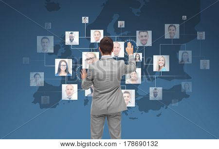 business, people, communication, cooperation and technology concept - businessman touching virtual screen with contacts icons and europe map over blue background