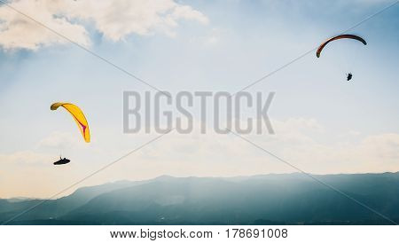 Two Paragliders Are Flying In The Valley.