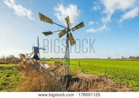 Small metal windmill and a large wooden hollow post mill together in a Dutch polder landscape on a sunny day in the fall season.