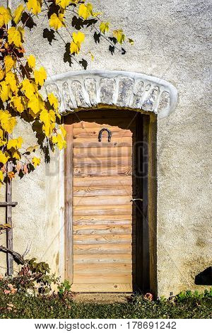 Old vintage wooden doors with horseshoe on a stone building. Weathered doors made of wooden planks and yellow vine leaves are closed.
