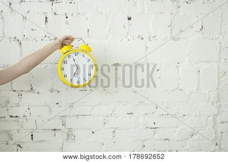 Girl holding yellow alarm clock in her hand isolated on white brick backgroung