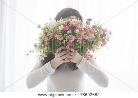 Young girl closed face with a bouquet of rose flowers, isolated on white background