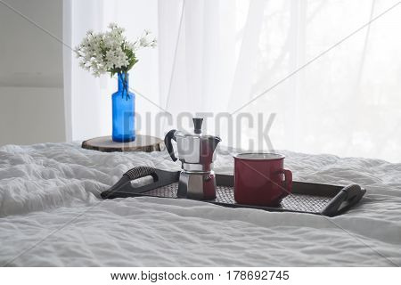 Cup of coffee with a blue vase on a wooden tray on white bed near window, hotel or home