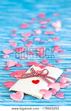 Nostalgic love letter with ribbon and many pink hearts around up to the blue background (copy space)
