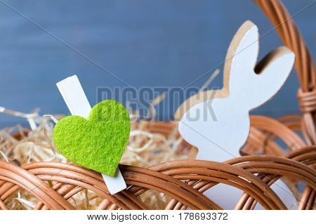 Greenery heart with spring easter bunny in wicker basket. Natural wooden background.