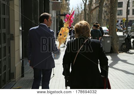 BARCELONA/ SPAIN - MARCH 29, 2015. A dapper man carrying a traditional decoration made of palm branches for Palm Sunday celebration at the Easter market. Barcelona, Spain