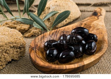 Black olives in wooden spoon, rusk and olive branch on sackcloth