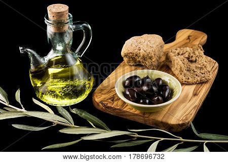Black olives, bottle of olive oil, rusk and olive branch on wooden chopping board on black background