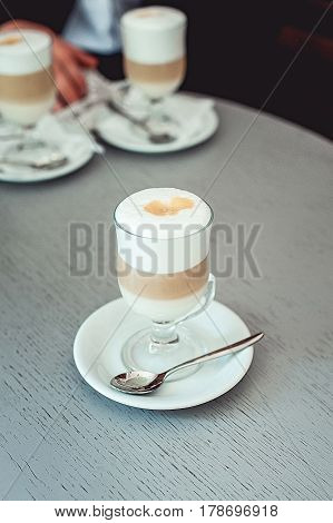 Fancy latte coffee in glass cup. Vintage table