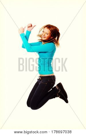 Young woman jumping with thumbs up