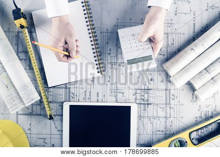 Workplace of architect. Rolls with building projects, equipment of architect: crash helmet and spirit level on wooden table.