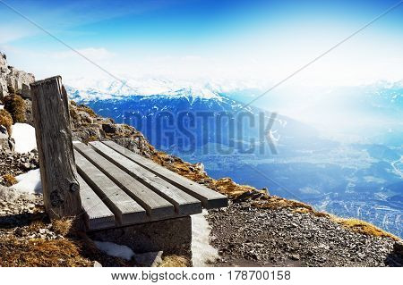 Travel or Vacation Concept. Wooden Bench behind Beautiful Mountain Landscape. Blue Sky. Alps Austria.