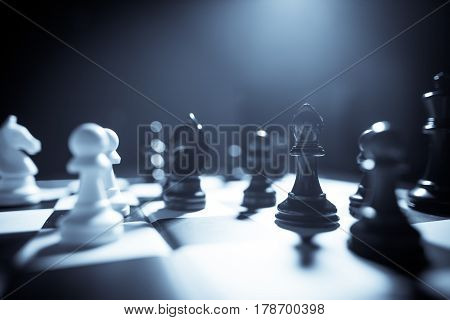 Image of the white and black pieces on a chess board with shallow depth of field.