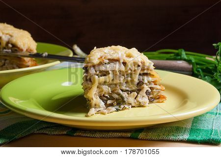 Piece Of Pancakes Pie With Mushrooms And Chicken Meat On Green Plate. Traditional Meal For Maslenits