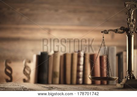 Law and justice concept - scale of justice and legal code on wooden background