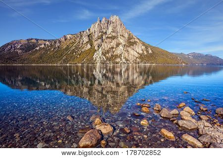 The water of shallow lake reflects sharp rocks. Picturesque mountain in Bariloche, Argentina. The concept of exotic and extreme tourism