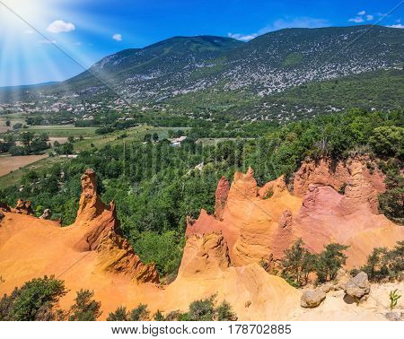 The sun strengthens the color of ocher. Unique red and orange hills in the province of Languedoc - Roussillon, France. The concept of ecological tourism