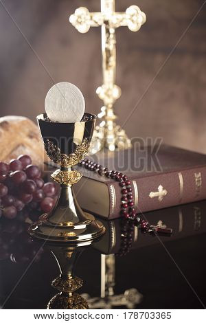 Catholic religion theme.  Holy Bible, the cross and gold chalice on glass table and stone background.