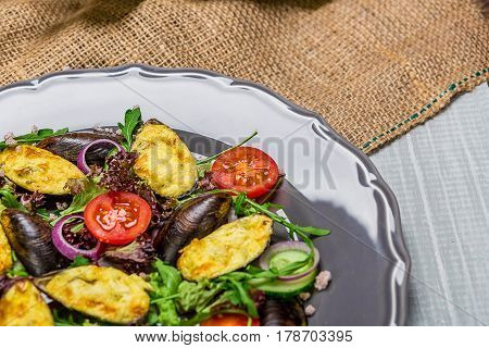 Fresh vegetable salad, healthy food, organic cucumbers, mussels, tomatoes and salad leaves. The original presentation of the dish from the chef