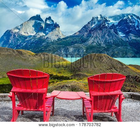Two comfortable red sun loungers overlooking the cliffs of Los Cuernos. Torres del Paine National Park. Summer in the south of Chile. The concept of extreme tourism