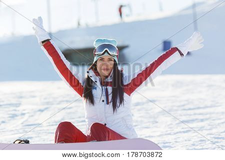 Beautiful athlete with snowboard on winter weekend in mountains