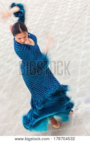Motion blurred slow shutter speed shot of a woman traditional Spanish Flamenco dancer spinning and dancing in a blue polka dot dress