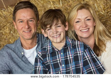 Portrait shot of an attractive, successful and happy family, middle aged man and woman couple with young boy child son sitting smiling together on hay or straw bales