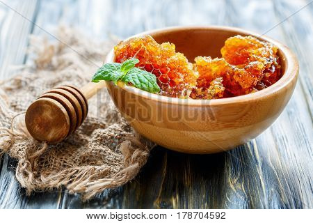 Honey In Honeycombs And Mint In A Wooden Bowl.