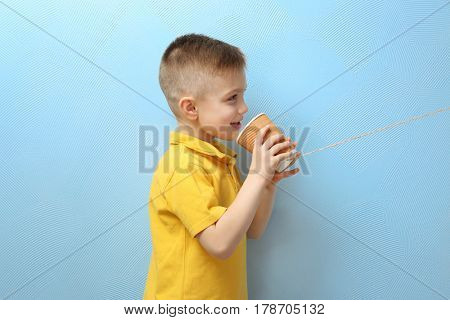 Cute little boy using plastic cup as telephone, on color background