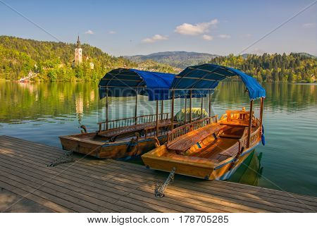 Traditional wooden tourist boats moored to the pier on Bled lake, Slovenia with pilgrimage church of the Assumption of Mary on Bled island in background