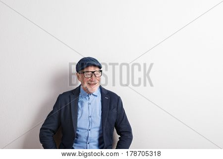 Handsome senior man in blue shirt, jacket, black eyeglasses and flat cap. Studio shot against white wall. Copy space.