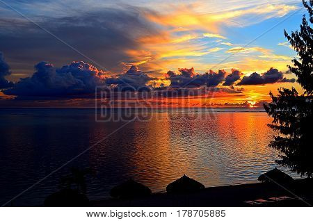 A fiery sunset over the Philippine Sea of Saipan Island, spilling with the beauty of the clouds, the blue sky and palm trees, encourages the weary traveler to relax on the beach
