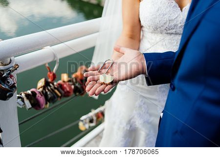Gold wedding lock in the form of heart in the hands of the bride and groom.