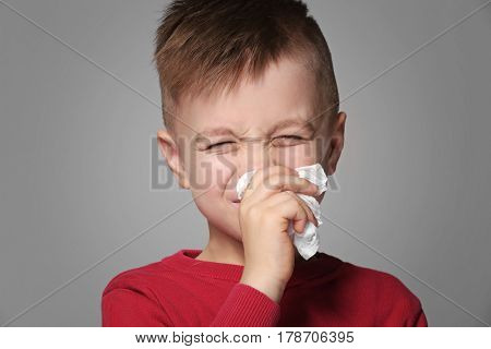 Cute little boy sneezing in tissue on gray background