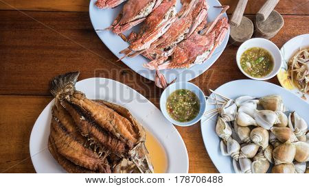 Steamed crabs , boiled sea snail and Deep crispy fried Sea bass with raw mango salad and spicy seafood sauce
