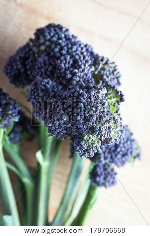 Close up of the head of a stalk of purple sprouting broccoli on a light wooden chopping board.