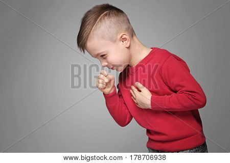 Cute little boy coughing on gray background
