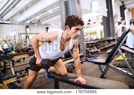 Young hispanic fitness man in gym on bench, working out with weights