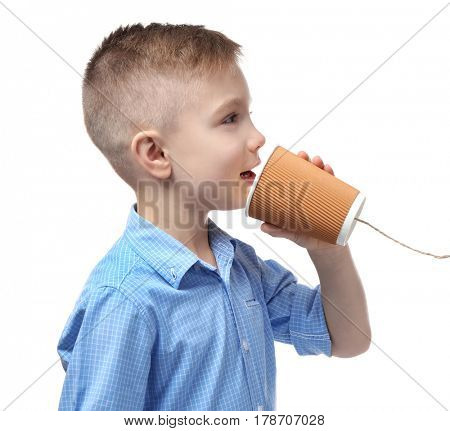 Cute little boy using plastic cup as telephone, on white background
